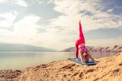 Frau, die in der Yogahaltung am Meer und an den Bergen meditiert Stockfotografie