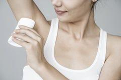 Frau, die desodorierendes Mittel auf ihrer Achselhöhle anwendet lizenzfreie stockbilder