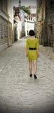 Frau, die in die alte Stadt von Tallinn geht Lizenzfreie Stockfotos