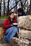 Frau, die die Bibel zum Kind lesend studiert Stockbild