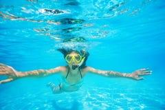 Frau, die die Maske schnorchelnd unter Wasser schwimmt trägt Stockfotos