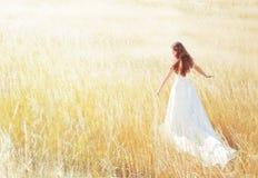 Frau, die in die sonnige Wiese am Sommertag geht Stockbild