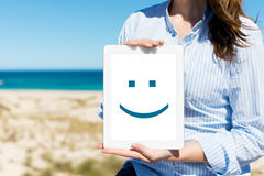 Frau, die Digital-Tablet mit Smiley Face At Beach anzeigt Lizenzfreie Stockfotos