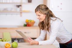 Frau, die digitale Auflage in der Küche verwendet Stockbild
