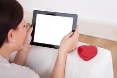 Frau, die digitale Tablette für on-line-Datierung verwendet stockfotografie