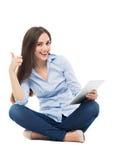 Frau, die digitale Tablette hält und sich Daumen zeigt Lizenzfreie Stockfotos