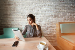 Frau, die digitale Tablette zu Suchinformation für bevorstehende Sitzung verwendet Stockbilder