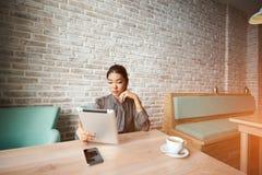 Frau, die digitale Tablette zu Suchinformation für kommende Sitzung verwendet Lizenzfreies Stockbild