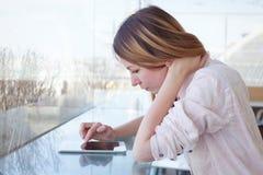 Frau, die digitales Tablettengerät in modernem Innen, E-Mail überprüfend verwendet lizenzfreies stockbild
