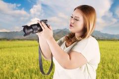 Frau, die Digitalkamera betrachtet Lizenzfreie Stockfotografie