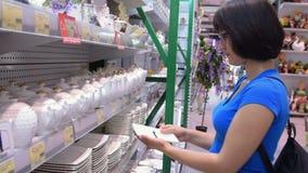 Frau, die Dishware im Speicher wählt stock video footage