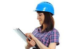 Frau, die Dokumente verwahrt und schützenden Blauhelm trägt Lizenzfreies Stockbild