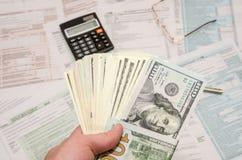 Frau, die Dollar auf einem Hintergrund von Steuerformularen hält Stockbild