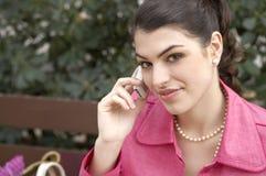 Frau, die draußen auf Handy spricht Stockbild