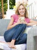 Frau, die draußen auf Patio mit Kaffee sitzt Lizenzfreies Stockfoto