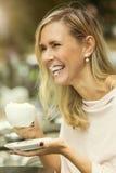 Frau, die draußen am Café lacht mit Schlagsahne auf ihr sitzt Stockfoto