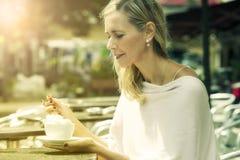 Frau, die draußen am Café mit Kaffee sitzt Stockbild