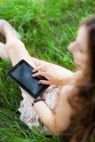 Frau, die draußen digitale Tablette verwendet Stockbilder