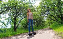 Frau, die draußen einen elektrischen Roller reitet Lizenzfreies Stockbild