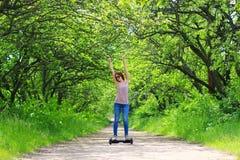 Frau, die draußen einen elektrischen Roller reitet lizenzfreie stockbilder