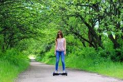 Frau, die draußen einen elektrischen Roller reitet stockbild