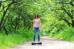 Frau, die draußen einen elektrischen Roller reitet stockfotos