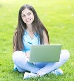 Frau, die draußen einen Laptop verwendet Stockbild