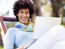 Frau, die draußen in einer Wiese mit Laptop arbeitet Lizenzfreies Stockfoto