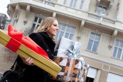 Frau, die draußen Geschenke geht Lizenzfreie Stockfotografie