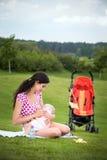 Frau, die draußen ihr Baby stillt Stockbilder