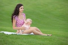 Frau, die draußen ihr Baby stillt Lizenzfreies Stockfoto