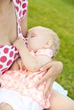 Frau, die draußen ihr Baby stillt Lizenzfreie Stockfotografie