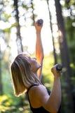 Frau, die draußen im Waldland ausarbeitet Stockbild