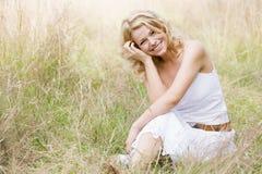 Frau, die draußen lächeln sitzt Lizenzfreie Stockfotos