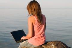 Frau, die draußen an Laptop-Computer arbeitet lizenzfreies stockbild
