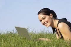 Frau, die draußen Laptop in der Sommer-Landschaft verwendet Lizenzfreie Stockfotografie