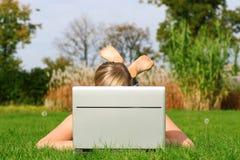 Frau, die draußen Laptop verwendet stockbild