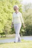 Frau, die draußen am Park durch das Seelächeln geht Stockbild