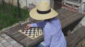 Frau, die draußen Schach spielt stock video