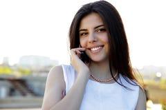 Frau, die draußen am Telefon spricht Stockbild
