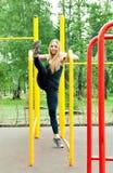 Frau, die draußen Training auf den Stangen ausübt Lizenzfreie Stockfotografie
