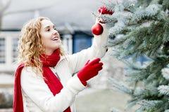 Frau, die draußen Weihnachtsbaum verziert Stockfotografie