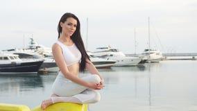 Frau, die draußen, Yogaübung, Baum-Haltung am Marine-Pier tuend ausarbeitet stock footage