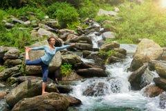 Frau, die draußen Yoga asana Natarajasana am Wasserfall tut Stockbilder