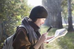 Frau, die draußen Karte mit Lupe betrachtet Stockbild
