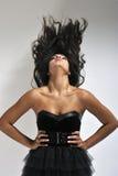 Frau, die dunkles Haar wellenartig bewegt Stockfotos