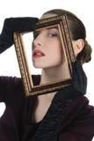 Frau, die durch Bilderrahmen schaut Stockbild