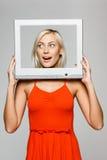 Frau, die durch Bildschirmfeld schaut Lizenzfreie Stockbilder