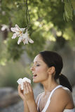 Frau, die durch Blumen niest Stockfoto