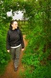 Frau, die durch Bogen in der Hecke in der Landschaft geht Stockbild